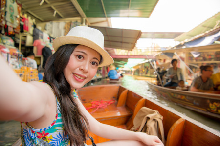 elegant attractive girl on river boat taking picture selfie and viewing floating market scene enjoying summer vacation during Thailand travel. Stock Photo