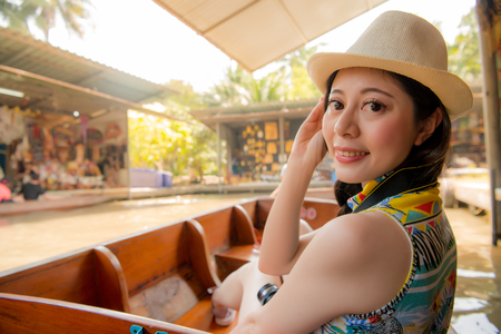 smiling beauty travel girl turn around to looking at camera when she travel in Damnoen Saduak floating market during Thailand travel. Reklamní fotografie