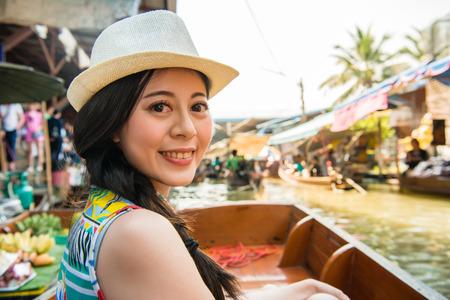smiling elegant woman traveler taking boat visiting Thailand Damnoen Saduak floating market and wearing hat looking at camera during vacation holidays. Stock Photo