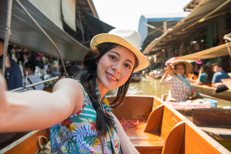 happy pretty girl tourist taking self-portrait photo selfie on boat when she visiting popular floating market during asia Thailand travel.