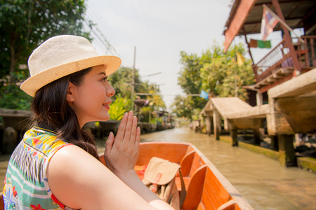 happy elegant woman traveler taking local river boat visiting floating market and making praying posing during asia Thailand vacation.