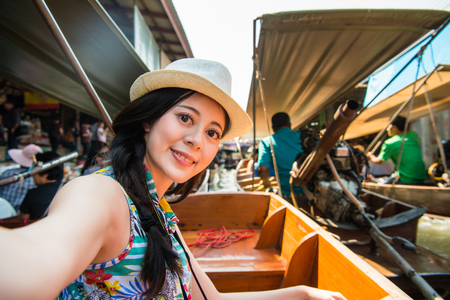 attractive young female tourist taking selfie on boat when she travel in Thailand and sightseeing famous floating market. Stock Photo