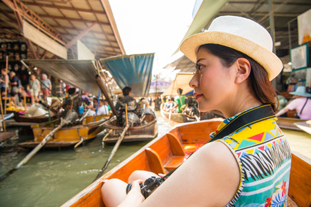 beautiful smiling woman going to Thailand travel and taking boat to viewing local river vendors in Damnoen Saduak floating market.