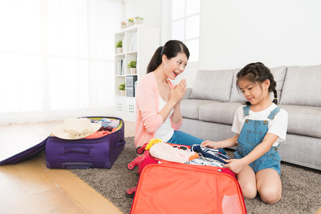 Pretty lovely little girl children packing personal travel luggage suitcase by herself and mother feeling happy praised her.