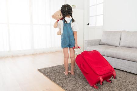 사랑을 껴안고있는 매력적인 귀여운 여자 아이의 다시보기 사진 거실에 서서 수하물 가방 함께 여행을 준비 들고 곰. 스톡 콘텐츠