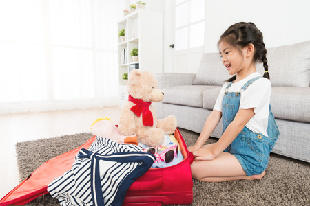 smiling young female little kid children finished prepared travel luggage suitcase and sitting on floor looking at teddy toy talking.