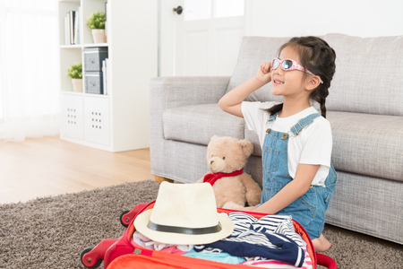 smiling happy girl children wearing sunglasses sitting on living room floor with teddy bear and finished packing luggage suitcase making daydreaming going to travel together.