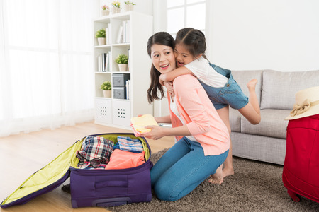 Happy girl hugging beautiful mother in living room feeling cheerful when woman packing luggage suitcase at home ready to travel.