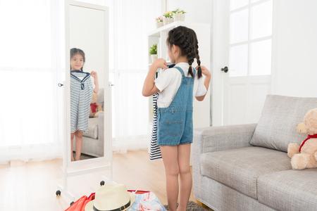 自宅で個人的な荷物のスーツケースを梱包し、リビングルームで旅行服を選択する鏡を見て幸せな若い女の子。