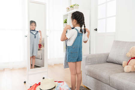 happy young little girl packing personal luggage suitcase at home and looking at mirror choosing travel clothing in living room.