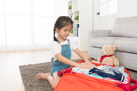 young beautiful female children organized luggage clothing in living room and packing personal travel suitcase prepared going travel with teddy bear.