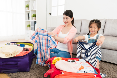 Smiling woman with young little daughter folding clothing together in living room and packing luggage ready to travel during summer vacation.