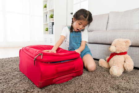 Beautiful young little girl finishing packing and closing luggage suitcase in living room finding overfilled feeling shocked. Stok Fotoğraf