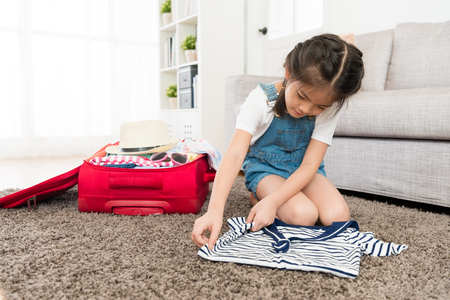 Young beautiful female children sitting on floor folding personal clothing and packing travel luggage suitcase by herself.