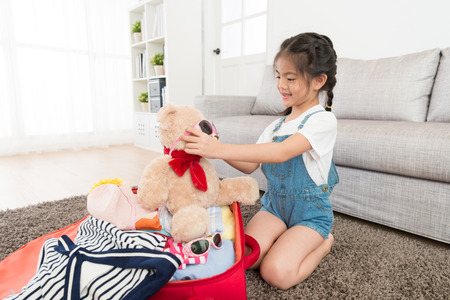 smiling pretty little girl packing luggage suitcase in living room and helping her love teddy bear toy wearing sunglasses ready to travel together. Фото со стока