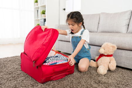pretty beauty female children opening personal travel luggage suitcase and looking at clothing finding wrong feeling surprised.