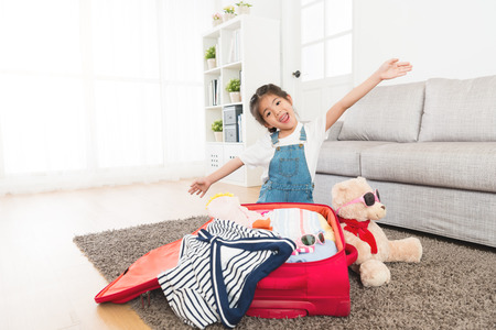 happy beautiful little kid sitting in living room floor with teddy toy and making fly gesture looking at camera when she packing travel luggage suitcase .