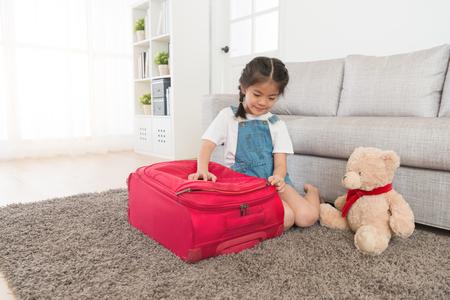Los niños hermosos de la muchacha de la belleza que se sientan en piso de la sala de estar terminaron el embalaje de la maleta y el bolso de viaje del equipaje de cierre listo para el viaje de las vacaciones de verano. Foto de archivo - 91779294