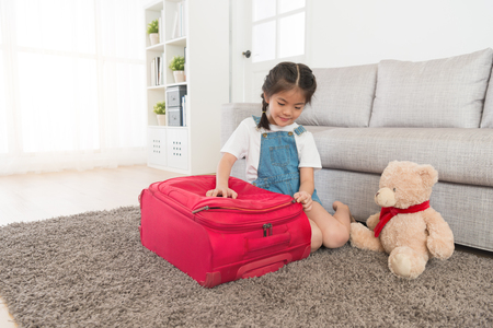 lovely beauty girl children sitting on living room floor finished packing suitcase and closing luggage travel bag ready to summer vacation trip. Stockfoto