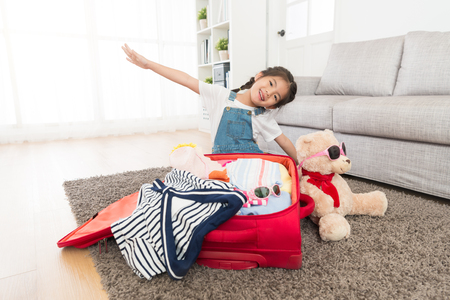 young lovely female children making airplane fly gesture looking at camera and packing travel luggage suitcase in living room floor with teddy toy.