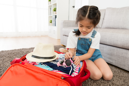 beautiful young little girl put sunglasses in travel luggage suitcase when she preparing go to trip with family during summer vacation.