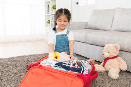 pretty beauty girl children kid sitting on floor packing personal travel luggage suitcase in living room at home with teddy bear toy. Stockfoto