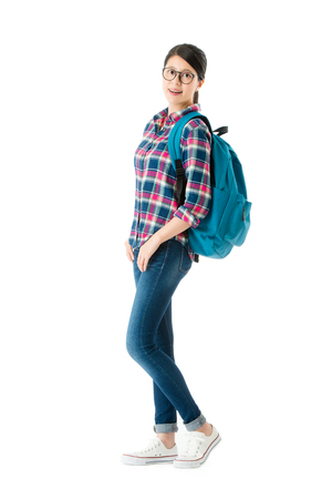 happy confident traveler woman ready to travel during vacation holiday and carrying personal baggage looking at camera isolated on white background. Stock Photo