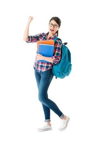 美しい甘い女子高生は、カメラを見て、白い背景に隔離された教科書で勉強袋を運ぶ応援ジェスチャーを示しています。