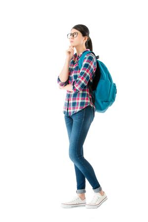 młoda ładna kobieta niosąc plecak szkolny stojąc na tle białej ściany i myśli o rozwiązaniu problemu badania edukacji.