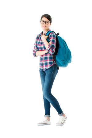 カメラに向かって個人的な勉強袋を運ぶ甘い魅力的な女子学生は、学校に戻る準備ができて白い背景に立っています。 写真素材