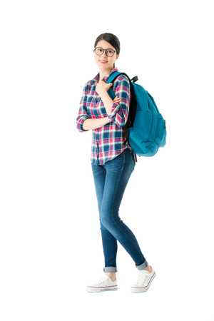 sweet attractive female student carrying personal studying bag face to camera and standing on white background ready back to school.