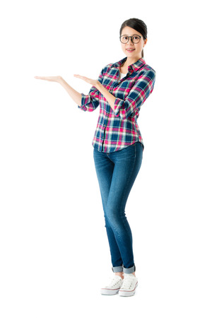 young happy female teacher standing on white background looking at camera and making present gesture showing empty area. 版權商用圖片