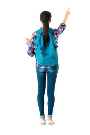 back view photo of pretty elegant girl college student pointing empty area standing on white background.