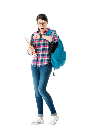 young pretty female student preparing back to school standing on white background and looking at watch finding late feeling shocked.