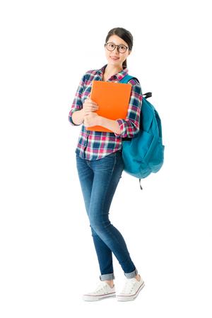 白い背景に立つ教育教科書を持つ魅力的な学生の笑顔。 写真素材