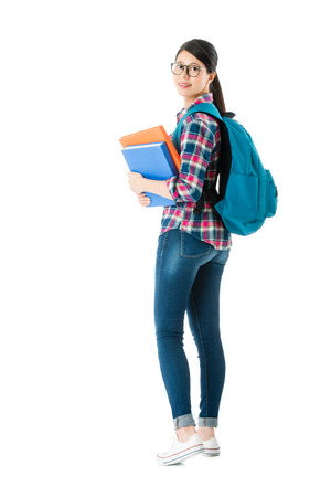young attractive student woman carrying textbook with bag turned around ready back to school studying isolated on white wall background.
