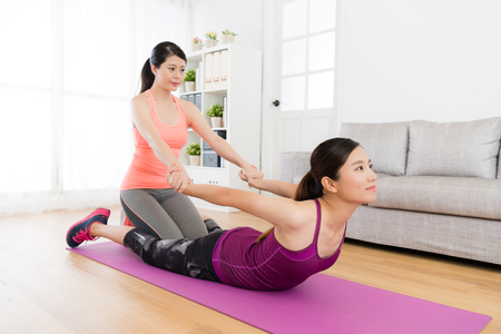 Professional young female fitness teacher pulling her student hands to stretch body and training softness when they having class at home. Stock Photo