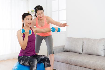 Attractive beauty female student sitting on yoga ball and holding dumbbell making boxing gesture workout body with her home fitness teacher.