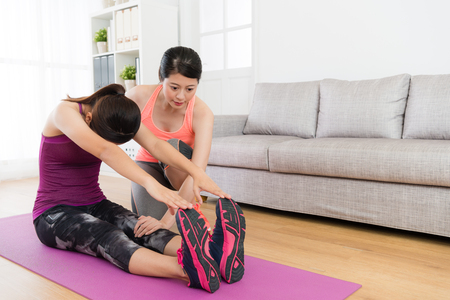 young beautiful female student stretching body and using hands touching legs training with her home fitness teacher in living room. Banque d'images