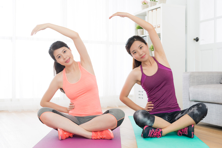 Smiling pretty women looking at camera doing yoga fitness warm up posture.