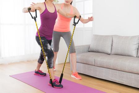 krachtige aantrekkelijke vrouwelijke fitness meisje met weerstand band trainingslichaam met haar workout leraar thuis.
