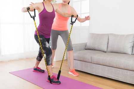 powerful attractive female fitness girl using resistance band training body with her workout teacher at home.