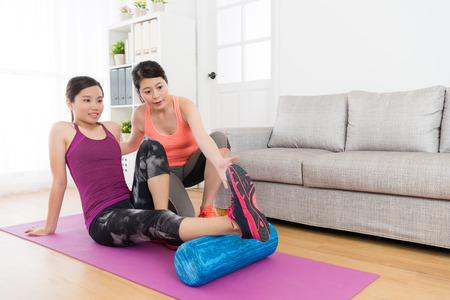 estudante fêmea bonito de sorriso que usa o rolo da ioga que faz o esporte da aptidão e seu professor home do exercício que ensinam como se exercitar.