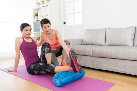 smiling beautiful female student using yoga roller doing fitness sport and her home workout teacher teaching how to workout. Stock Photo