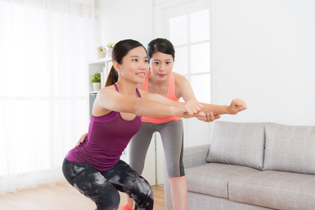 confident young home fitness coach teaching smiling beauty girl workout body and making squatting to train endurance with balance. Foto de archivo