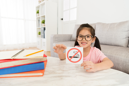 smiling lovely little girl looking at camera presenting no smoking notice.