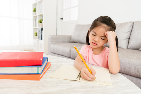 traurige unglückliche kleine weibliche Kinder, die englische Hausaufgaben schreiben, bevor sie sich wieder in die Schule begeben. Standard-Bild