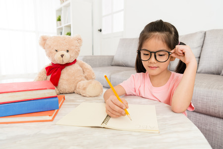 smiling beauty female kid student studying at home with teddy bear and writing school homework preparing back to school.