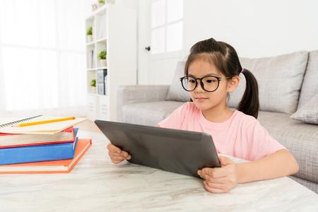 Attrayante jeune enfant femelle enfants assis dans le salon à la maison et à l'aide de tablette numérique mobile, regarder des vidéos en ligne. Banque d'images - 92348670
