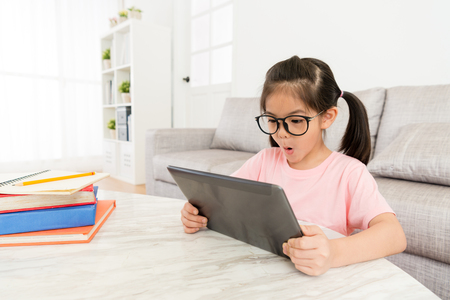 beautiful young girl children using mobile pad computer looking online funny video feeling cheerful when she finished school textbook studying.